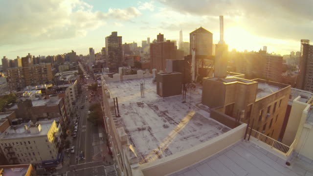 WS AERIAL SLO MO View of water tower with city scape at Sun setting / New York, United States