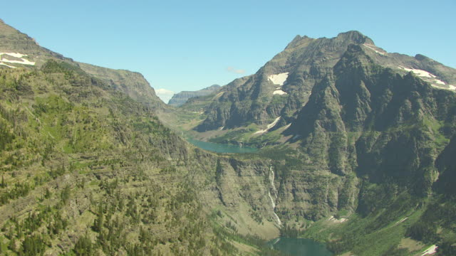 WS AERIAL View of waterfall near Lake Ellen Wilson in Glacier National Park / Montana, United States