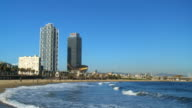 WS TU View of waves crashing on Barceloneta beach in front of Arts and Torre Mapfe hotels / Barcelona, Catalonia, Spain