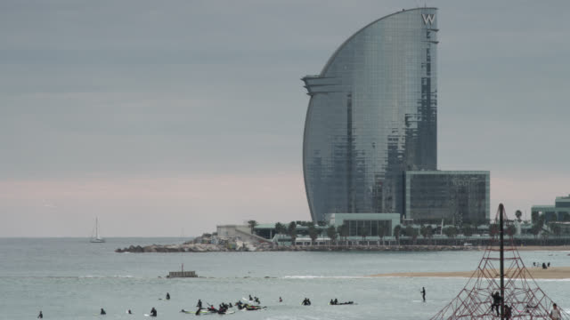 WS View of Wella building skyline on shore with awaiting surfers / Barcelona, Catalunya, Spain