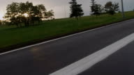 View of wet asphalt and dividing lines on highway during sunset from car in motion