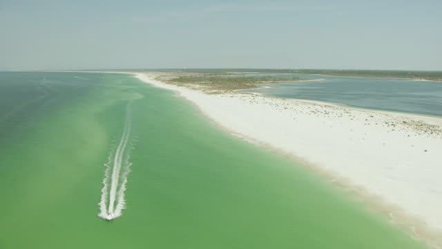WS AERIAL View of white sand beaches and single boat driving along beach in panhandle / Florida, United States