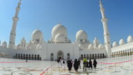 MS View of White Sheikh Zayed Grand Mosque in Abu Dhabi in UAE with Muslim tourists / Abu Dhabi, United Arab Emirates