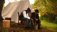 WS View of white Union soldier and black man sit together next to tent and thresh corn / Culpeper, Virginia, United States
