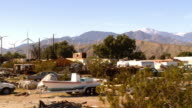 WS PAN View of wind turbine farm with junkyard in foreground / Palm Springs, California, USA