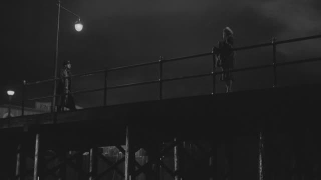 WS LA View of Woman waiting for man on bridge