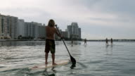 WS View of women and man riding paddle boards in harbor / Miami Beach, Florida, USA