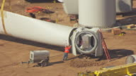 MS AERIAL DS View of workers on ground fitting blade to hub of wind turbine generator at flat ridge wind farm in Harper County / Kansas, United States
