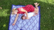 WS View of young girl laying with her baby brother outside / Lamy, New Mexico, United States