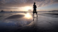 WS SLO MO POV View Of young man jogging on beach at Sun setting / Hubbard Beach, Oregon, United States