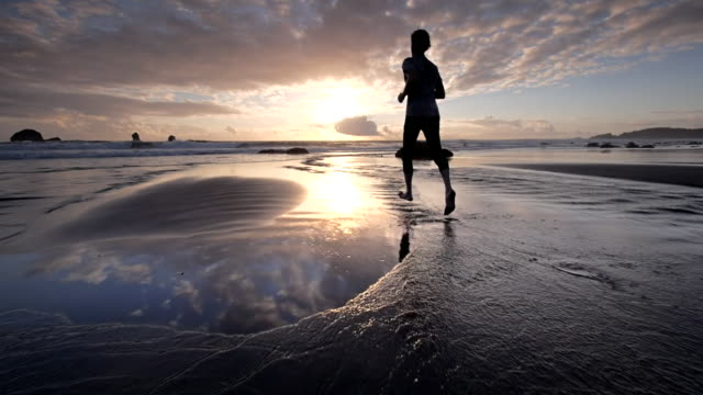 WS SLO MO POV View Of young man jogging on beach at Sun setting / Hubbard Beach, Oregon, United States