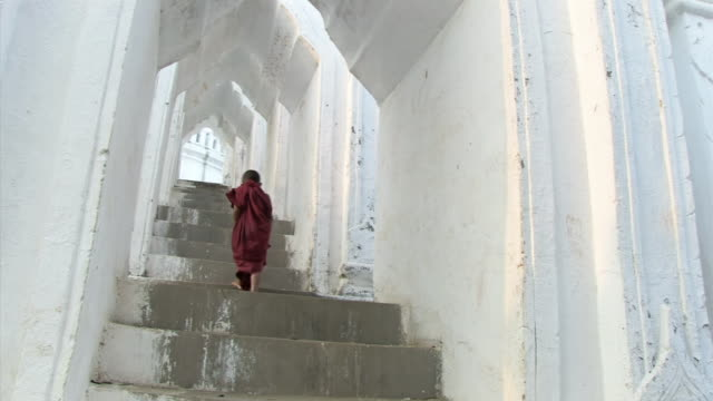 WS View of young monk climbing up some stairs  / Mandalay, Mandalay Division, Myanmar