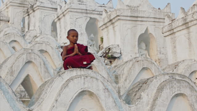 WS View of young monk praying, sitting on huge white temple steps  / Mandalay, Mandalay Division, Myanmar