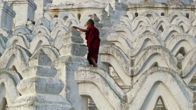 WS View of young monk walking across huge white temple steps from left to right  / Mandalay, Mandalay Division, Myanmar