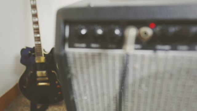 View on amplifier knobs, plugs and electric guitar