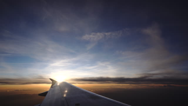 View out of airplane window to sunrise over wingtip