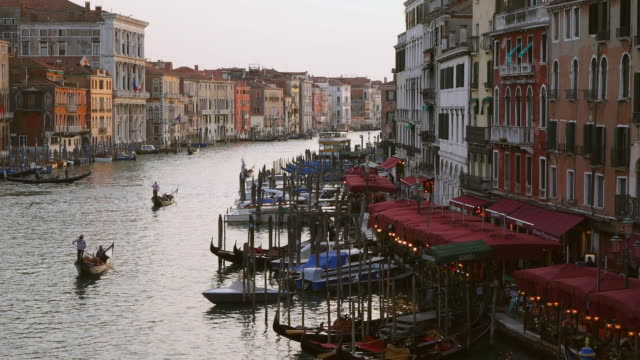 WS HA View over Canal Grande near Ponte di Rialto with cafes on side and gondolas sailing at sunset / Venice, Veneto, Italy