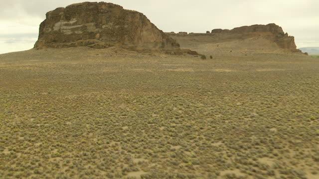 MS AERIAL View over desert landscape to reveal Fort Rock volcanic rock formation / Oregon, United States