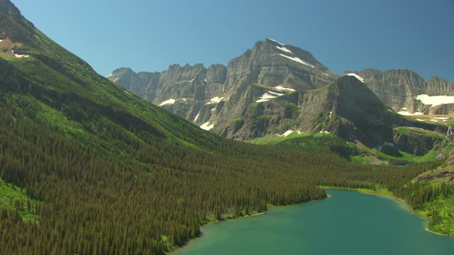 WS AERIAL View over edge of Swift current Lake with glaciers and mountains at Glacier National Park / Montana, United States