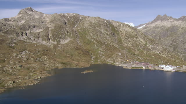 WS PAN AERIAL View over Grimsel Pass road and Totesee reservoir on pass with Hotel Alpenrosli and Lake Grimsel with Summit of Sidelhorn / Grimsel Pass, Valais, Switzerland