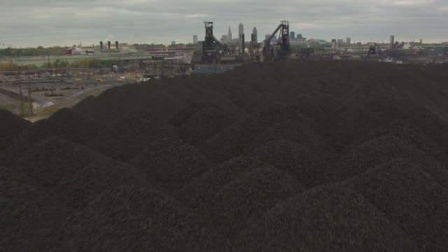 MS TU AERIAL View over mountains of coal to Arcelor Mittal Steel plant with downtown skyline / Cleveland, Ohio, United States