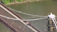 MS TS AERIAL View over pedestrians walking on Wheeling Suspension Bridge with cars driving by bridge / Wheeling, West Virginia, United States