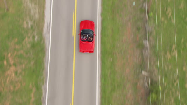 MS AERIAL TS View over red and black Corvettes driving on country road / Bowling Green, Kentucky, United States