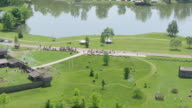 WS TS AERIAL View over Shawnee line runs forward and fires guns in field at Fort Randolph Reenactment / Point Pleasant, West Virginia, United States
