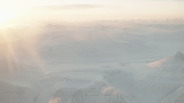 WS AERIAL View over sun bright snowy landscape / Svalbard, Norway