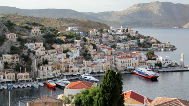 View over Symi town and Harbourwith the Towns traditional homes and pastel colours, Aegean Sea, Greece, Europe