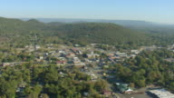 WS AERIAL View over town buildings nestled in rolling forested landscape / Scottsboro, Alabama, United States