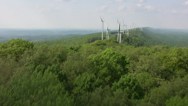 WS AERIAL View over trees to reveal row of Laurel Mountain Wind Farm in Randolph County / West Virginia, United States