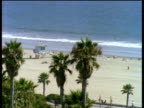 View overlooking quiet Santa Monica beach with lifeguard station and American flag flying tops of palm trees in foreground