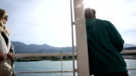 View past man to woman on ferry boat, leaving harbour