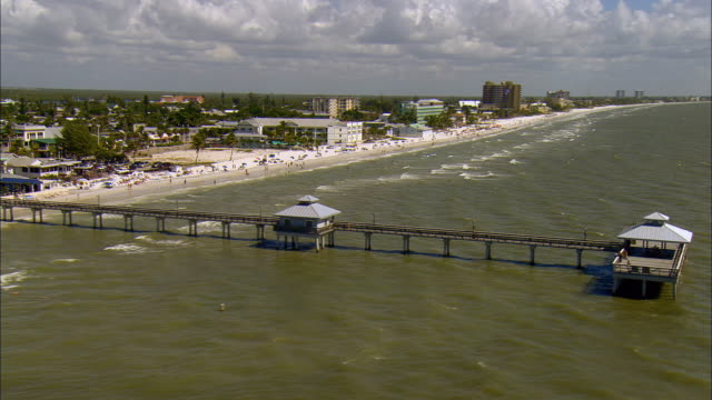 AERIAL WS View past pier, beach and hotels along Gulf coast / Fort Myers Beach, Florida, USA