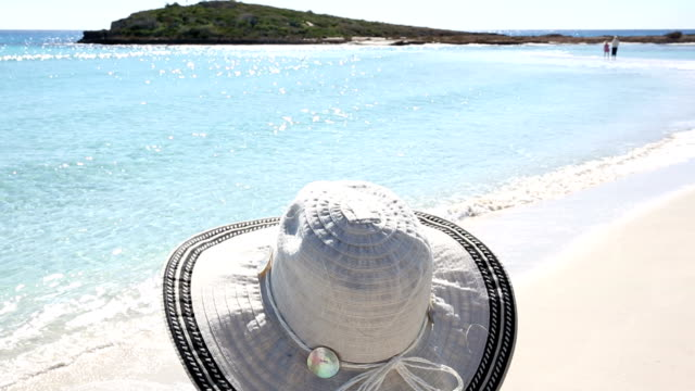 View past woman's hat to perfect white sand beach