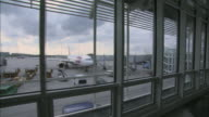 WS View through airport window of passenger jet attached to boarding bridge/ Munich, Germany