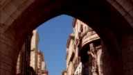View through archway of La Grosse Cloche of buildings on clear day / Bordeaux, France