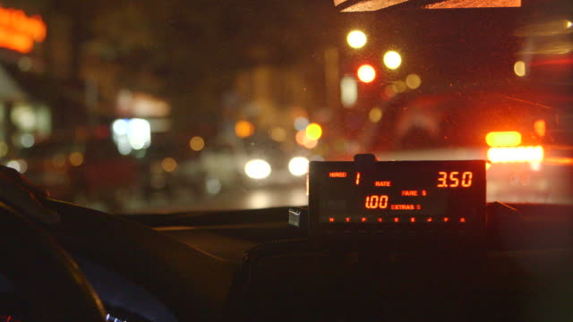 View through the dashboard of a New York City taxi at night