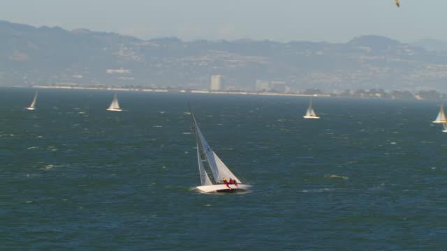 WS DS ZI AERIAL View to people in sailboat near Alcatraz Island and prison complex / San Francisco, California, United States