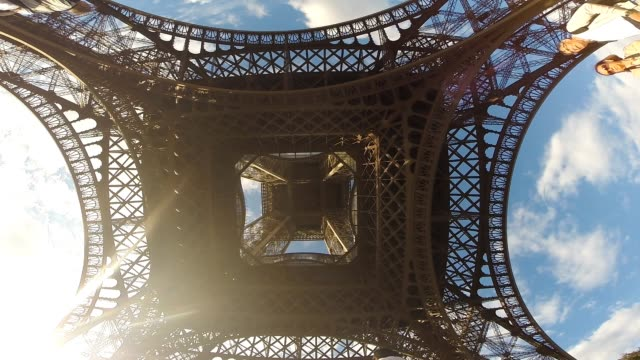 View under the Tour Eiffel in Paris with wide angle lens recorder from the ground to catch all the construction with the tourists visiting the place...