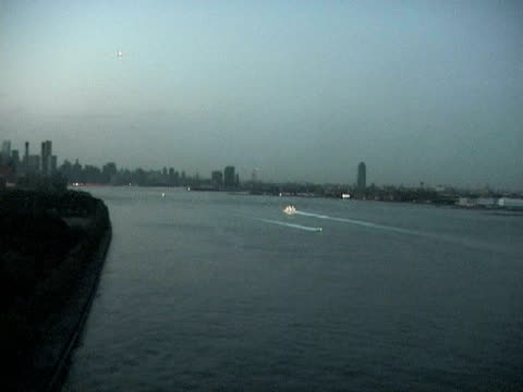 Views at dusk from bridge FDR Empire State Bldg boat on river BQE Manhattan skyline all dark except for car lights