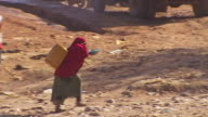 Views of a street in Baidoa Somalia where people are collecting water from a communal well