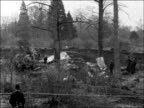 Blackbushe EXT 2 aerial views wreckage of plane in woods / 2 ground shots ditto / MS police and wreckage / 2 CSs wreckage of plane / Pan shot along...