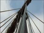 Vikings raise sail up mast on long ship Norway