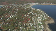 AERIAL Village on headland jutting out into bay, with some autumn foliage and a sheltered bay beyond / York, Maine, United States