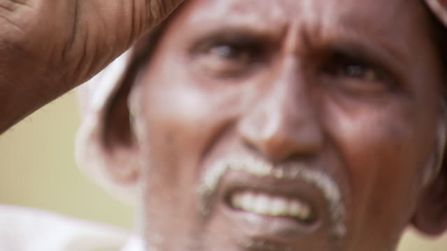CU TU R/F Villager holding small rock at eye level and inspecting it against light / Kollur, India