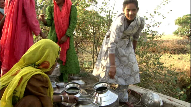 A villager pours water into pails in India.