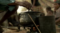 A villager stirs a cooking pot over a fire. Available in HD