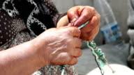 HD: Villager woman is knitting socks